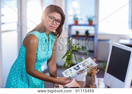 Smiling casual businesswoman working with photos in the office