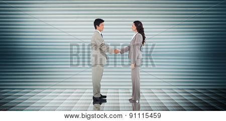 Business people shaking hands against grey shutters