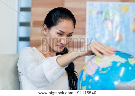 Pretty businesswoman looking at globe in the office