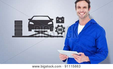 Handsome mechanic holding digital tablet against grey vignette