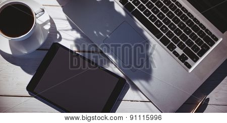 Overhead shot of laptop and tablet on a desk