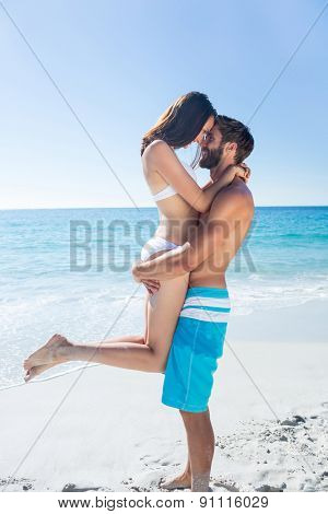 Handsome man carrying his girlfriend at the beach