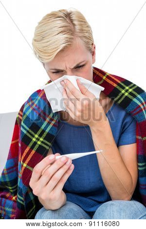 Sick blonde woman blowing her nose and checking the thermometer on white background