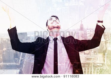 Businessman cheering with hands raised against new york skyline