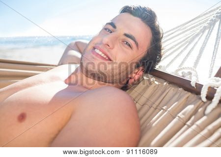 Handsome man relaxing in the hammock and smiling at camera at the beach