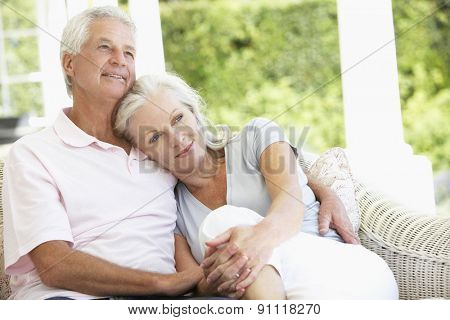 Senior Couple Relaxing On Seat Outside House