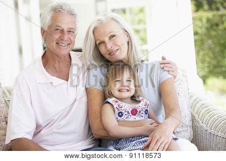 Grandparents Relaxing On Seat With Granddaughter