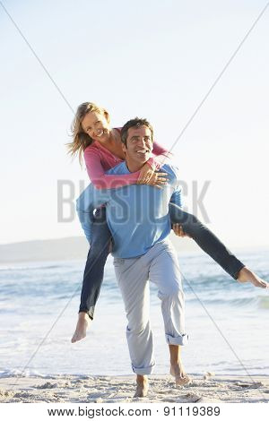 Man Giving Woman Piggyback On Beach