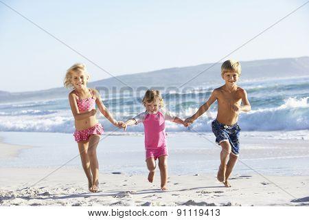 Group Of Children Running Along Beach In Swimwear
