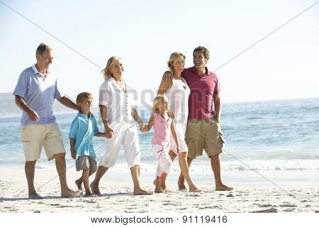 Three Generation Family On Holiday Walking On Beach