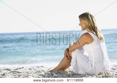 Young Woman Sitting On Sandy Beach