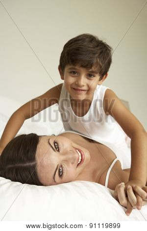 Mother And Son Relaxing On Bed