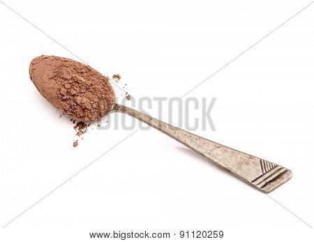 cocoa powder in a metal spoon isolated on white background