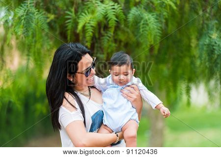 smiling young mother playing with her cute baby  in the garden on a sunny summer day