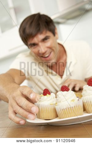 Man Eating Cakes In Kitchen