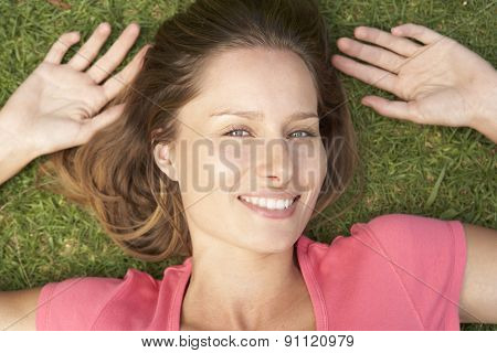 Overhead Of Smiling Woman Lying On Grass