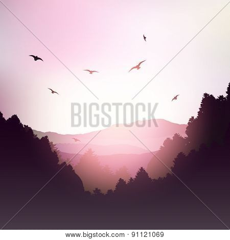 Landscape of mountains and trees against a sunset sky