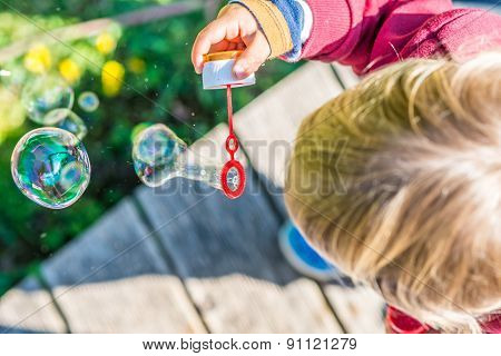Young Blond Child Blowing Bubbles