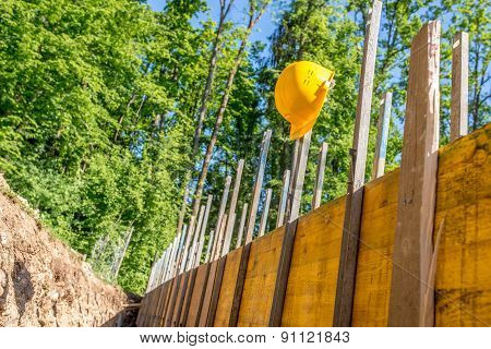 Yellow Hard Hat On Post At Building Site