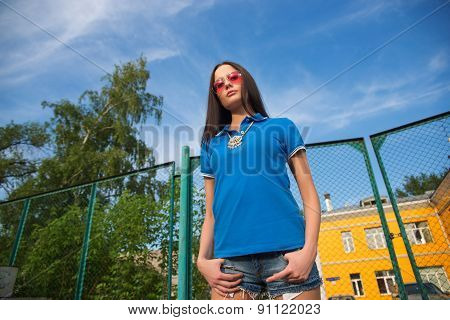 young woman posing outdoor over fence mesh