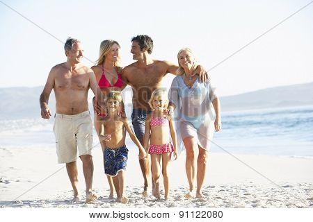 Three Generation Family On Holiday Walking Along Beach
