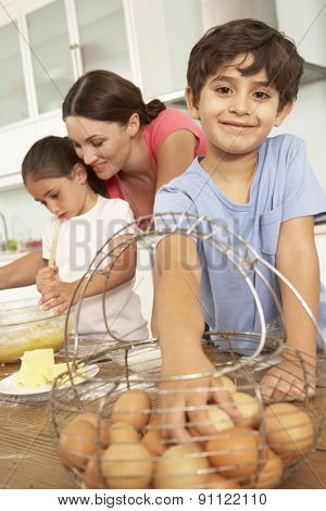 Children Helping Mother To Bake Cakes In Kitchen