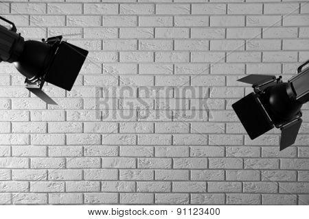 Photo studio with lighting equipment on brick wall background