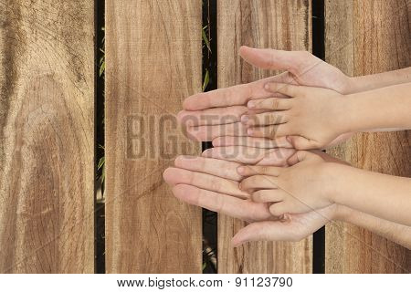 Father And Son Holding Hands On Wooden Background