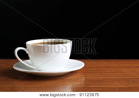 Cup of coffee on table on dark background