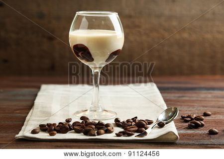 Glass of tasty panna cotta dessert on plate, on wooden table
