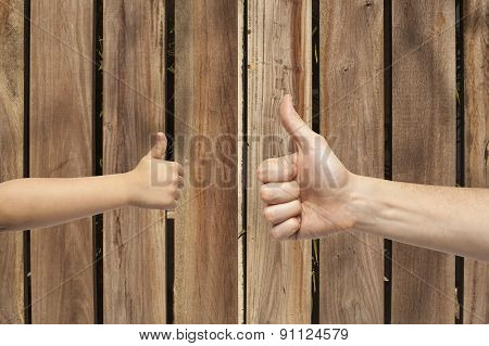 Father And Son Hands Giving Like On Wooden Background