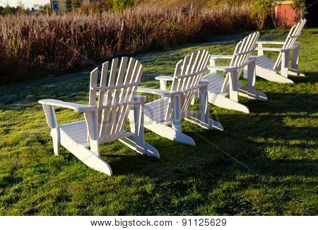 White Adirondack chairs in a row with evening light.