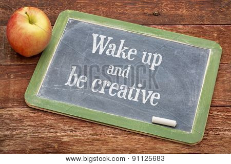 Wake up and be creative  - inspirational positive words on a slate blackboard against red barn wood