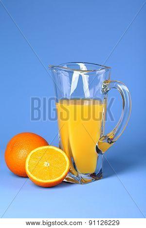 Glass pitcher of orange juice on blue background