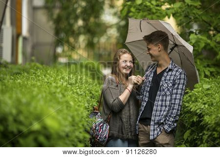 Young couple guy and girl outdoors under a umbrella in the small rain.