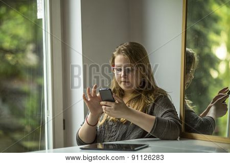 Teenage girl at glasses with smartphone sitting near the window.