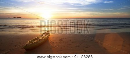 Panorama at ocean beach, canoe lying on the shore during wonderful sunset .