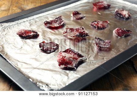 Candied sugared roses petals on foil, on wooden background