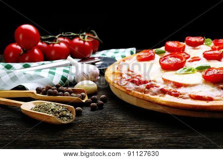 Delicious pizza with cheese and cherry tomatoes on wooden table on dark background