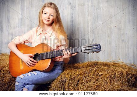 Beautiful girl teenager in shirt and torn jeans playing guitar sitting on hay. Jeans fashion. Western style.
