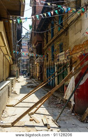 KATHMANDU, NEPAL - MAY 14, 2015: A small alley off Freak Street where wood beams support damaged buildings after two major earthquakes hit Nepal in the past weeks.