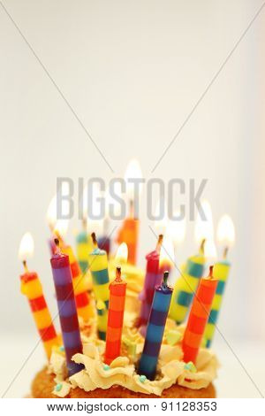 Delicious birthday cupcake on light background
