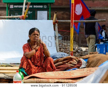 KATHMANDU, NEPAL - MAY 14, 2015: A Nepalese woman sits in a makeshift campsite after two major earthquakes hit Nepal in the past weeks.