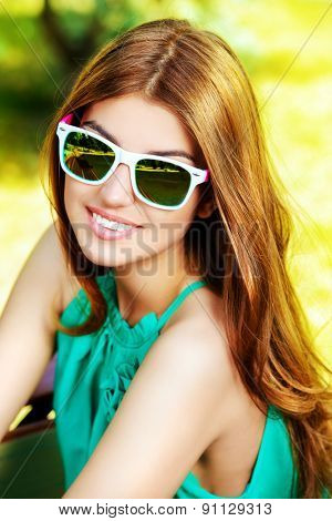 Happy young woman with beautiful smile outdoors. Summer day.