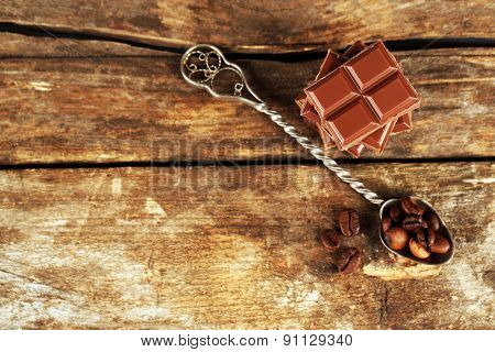 Pieces of chocolate and coffee beans in spoon on wooden background