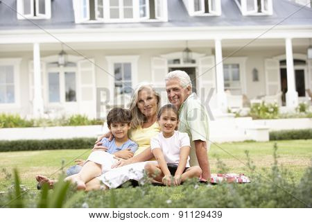 Family Sitting Outside House On Lawn