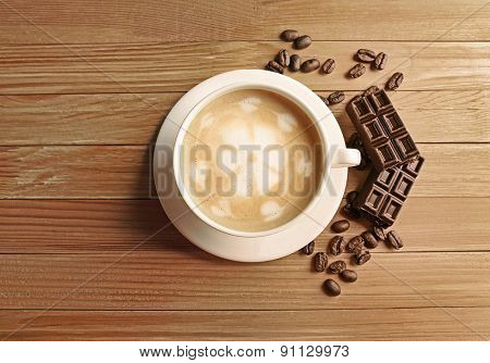 Cup of coffee latte art with grains and chocolate bars on wooden table, top view
