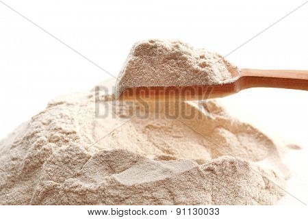Heap of flour with wooden spoon close up