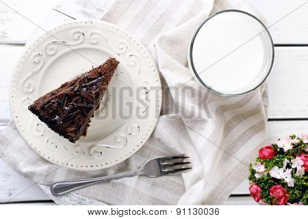 Sliced tasty chocolate cake in plate and glass of milk on color wooden table background, closeup