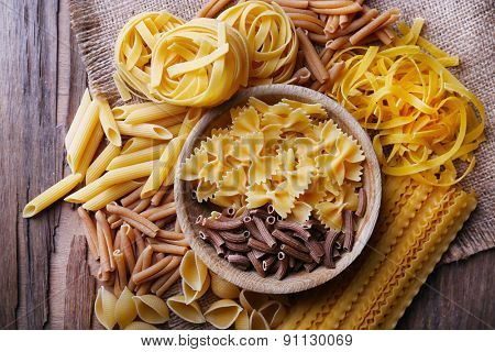 Different types of pasta on rustic wooden table